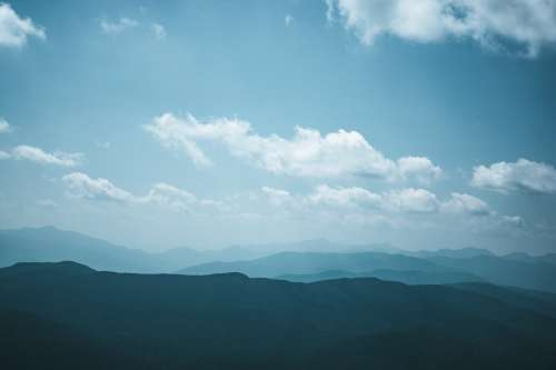 White Clouds In A Blue Sky Over Hills Photo