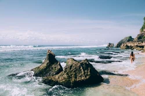 Woman In Bikini Walks Along Sandy Beach Photo