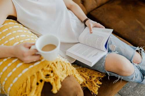 A woman with a cup of coffee reads a book