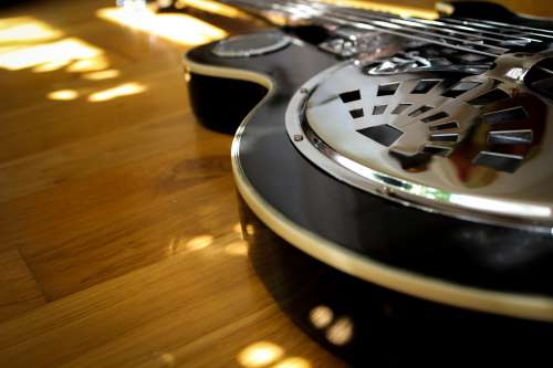 A Black Guitar Reflects Sunlight Onto The Wooden Floor Photo