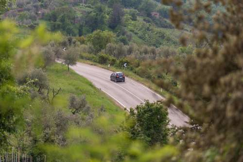 A Car Winds Round A Curve On A Highway On A Hill Photo