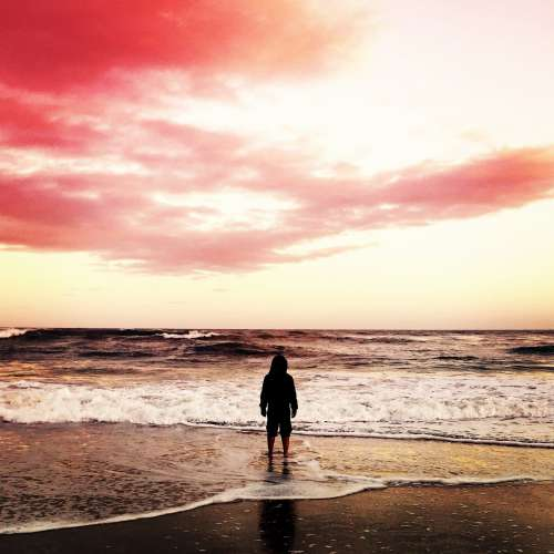 A Figure In A Hoodie On A Beach At The Shoreline Photo