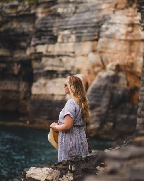 A Woman In A Summer Hat Stands On A Cliff Photo