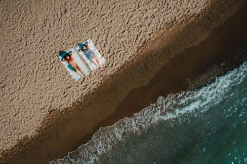 Aerial View Of Sandy Beach With Two Women Laying On Blankets Photo