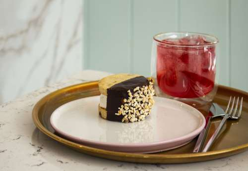 An Ice Cream Sandwich And A Glass Of Juice On A Tray Photo