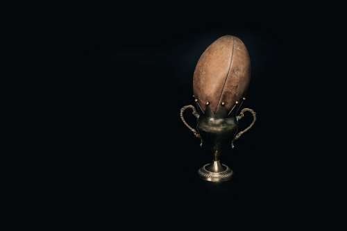 An Old Leather Football And Trophy Photo