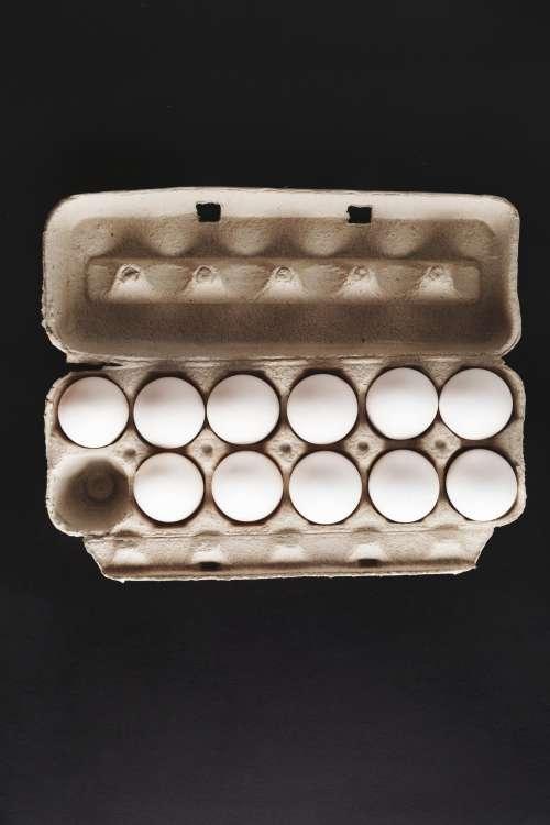 Eleven Eggs In Cardboard Carton On Black Background Photo