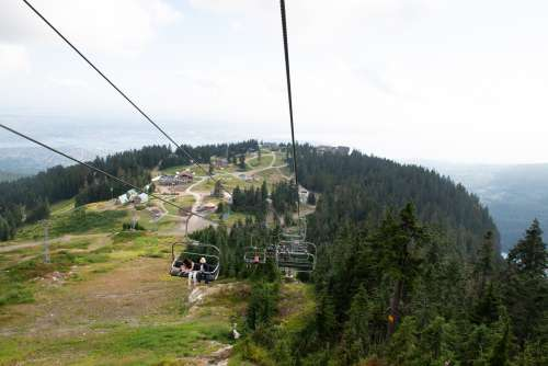 Happy Tourists On A Chairlift In The Mountains Photo