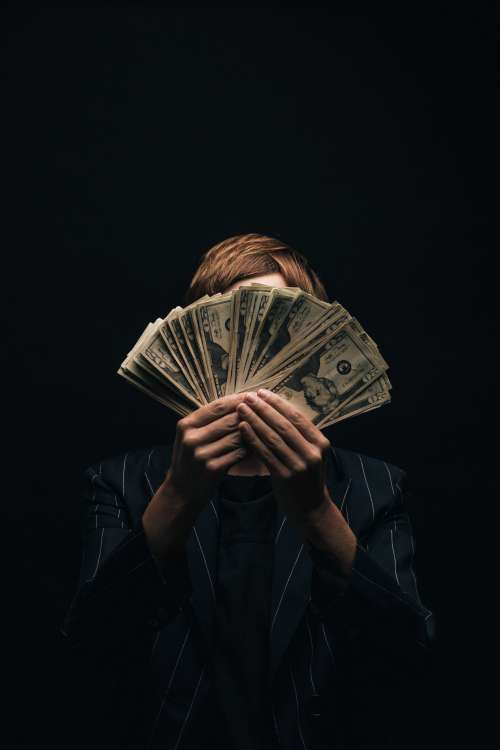 Person Holds Money In Front Of Face Photo