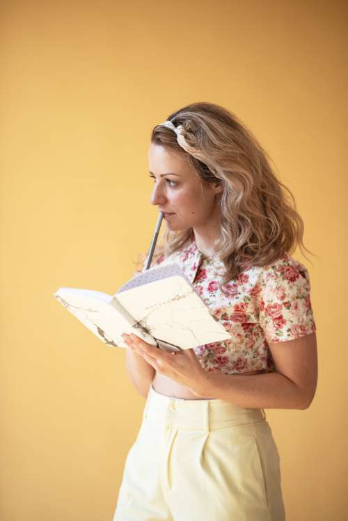 Young Woman Deep In Thought With Book Photo