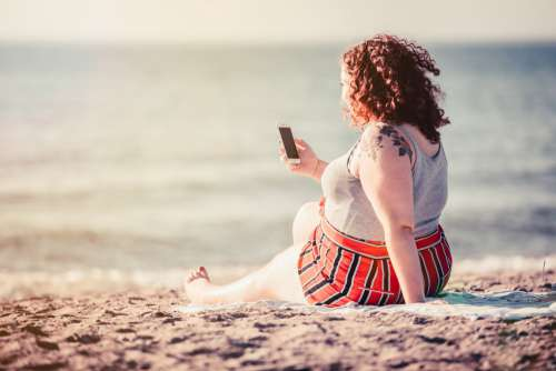 Young Woman Looks At Phone While Sitting On Beach Blanket Photo
