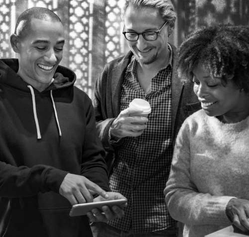 Multiethnic colleagues looking at mobile phone - black and white