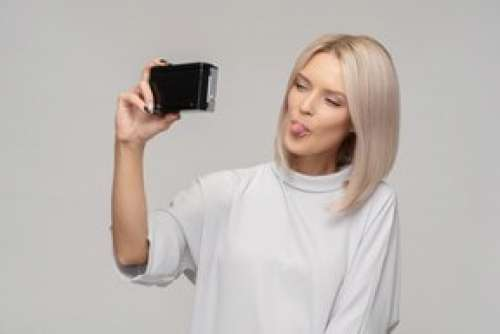 Young Woman Taking A Selfie With An Old Camera And Showing A Tongue