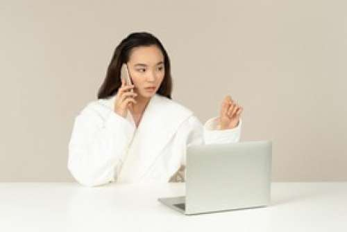 Young Asian Woman Talking On The Phone And Using Laptop