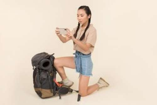 Outraged Young Asian Woman Standing Near Backpack And Taking Picture With Smartphone