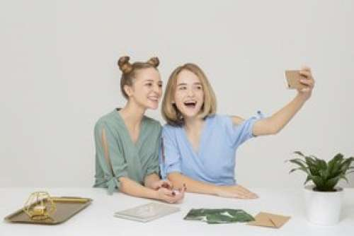 Two Smiling Girls Sitting At The Table And Making A Selfie