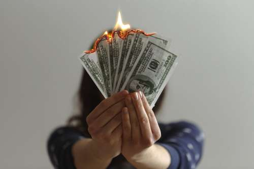 Hand Holding Bills on Fire