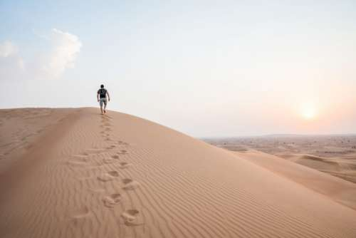 Man Walking Up Sand Dunes