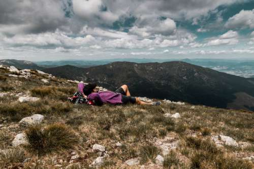 Carefree happy woman lying on green grass meadow on top of mountain