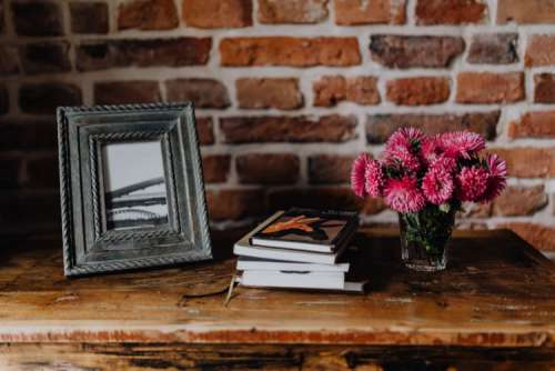 Photo frame, books and pink flowers in a vase on a wooden commode