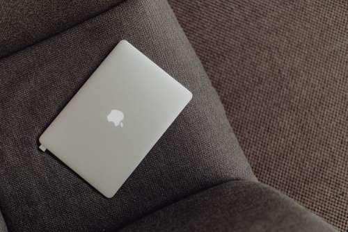 Close up view of closed laptop lying on grey armchair