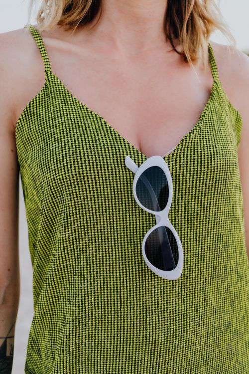 A woman in a green dress on the beach with white sunglasses