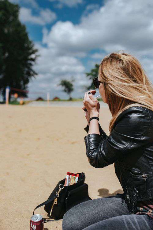 Young woman wearing a leather jacket and sunglasses on the beach