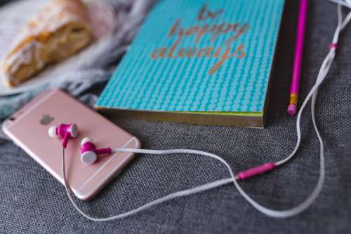 Blue notebook with a pink iPhone, headphones and a sweet bun