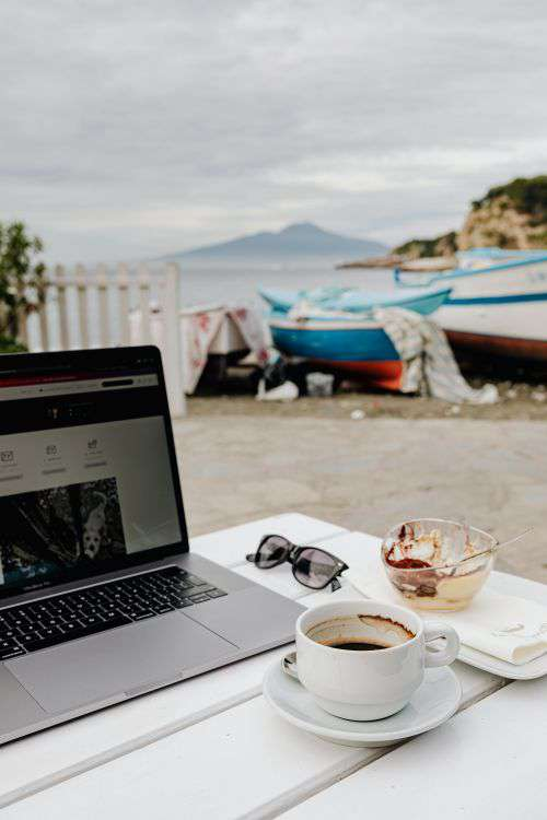 Working with a laptop by the sea. Cup of coffee and delicious tiramisu, Marina di Puolo, Italy