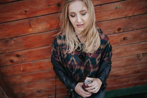 Blonde woman with a can of coke by a wooden wall