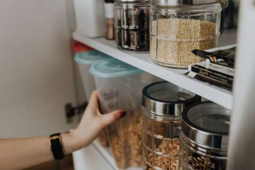 Containers of cereals in kitchen cupboard