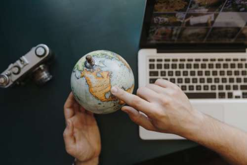 Male Finger Showing A Part Of The World On An Globe