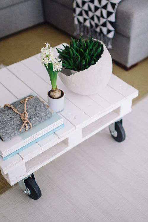 Small wooden table with a potted plant and a grey wallet