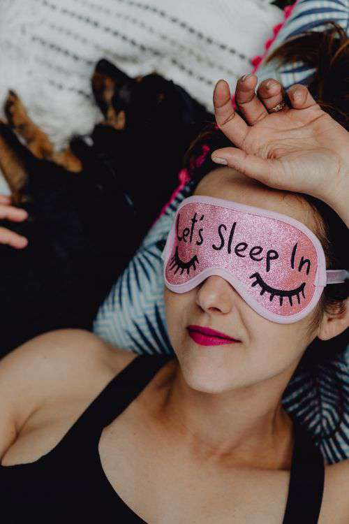 Joyful girl relaxing in bedroom - top view of brunette women in pink sleeping mask