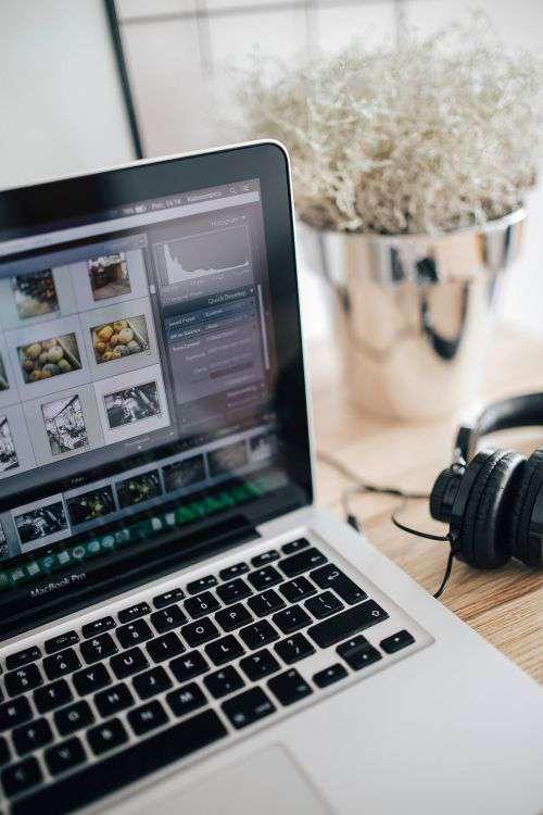 MacBook Pro with headphones on a wooden desk