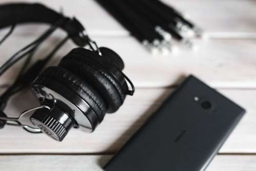Black smartphone and headphones with various items