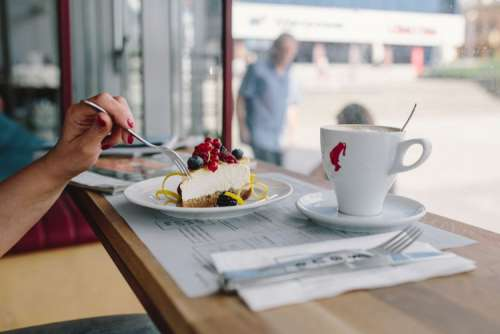 Woman Enjoying Cheese Cake and a Coffee with Fruits in a Cafeteria