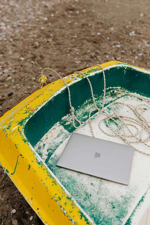 Macbook laptop on a small yellow boat on the beach