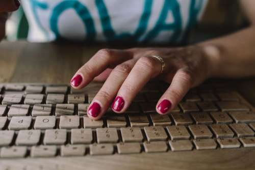 Closeup of female hands typing text on a wireless wooden keyboard