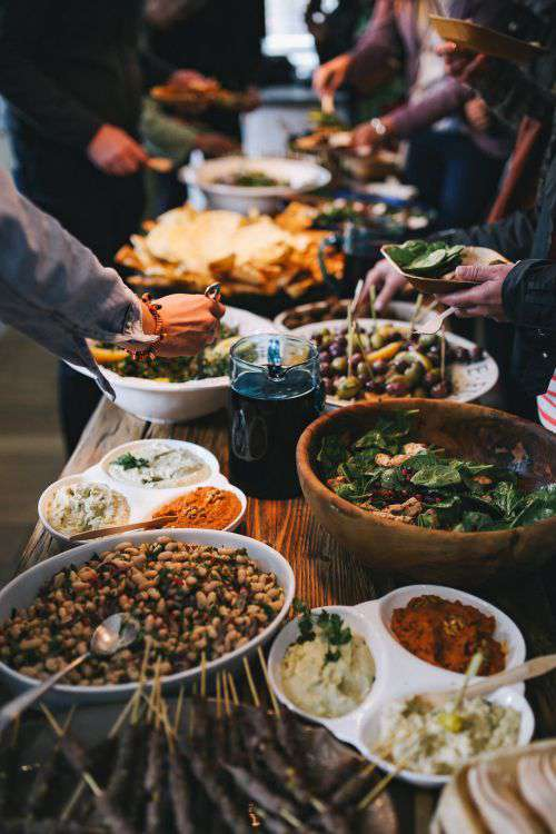 People by a banquet table full with food