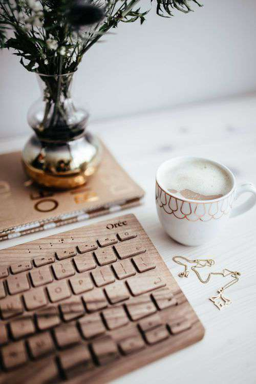 Wooden keyboard and cup of coffee