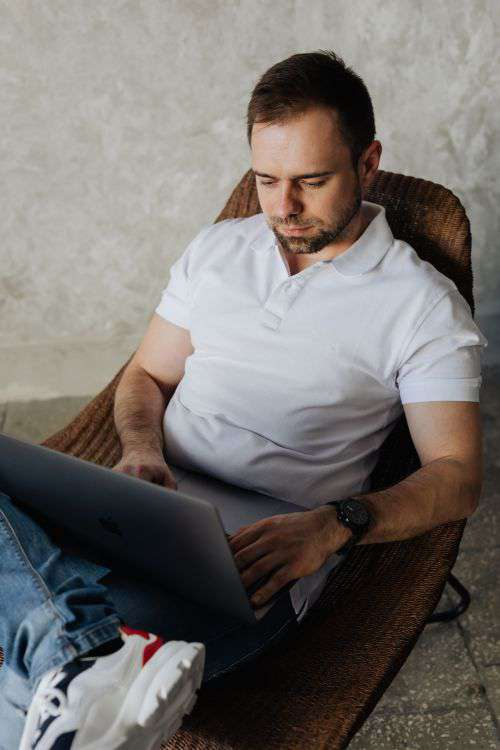The man is sitting in a chair and working with a laptop