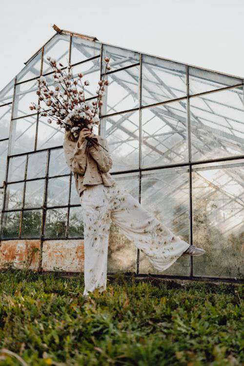 A beautiful tall woman holds cotton branches