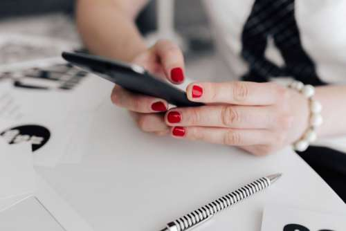 Businesswoman uses her mobile phone at her desk