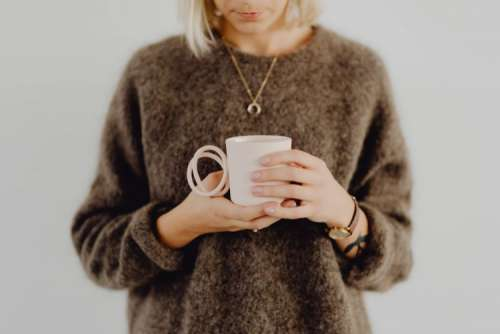 A woman in a brown sweater holds a pink, minimalist mug