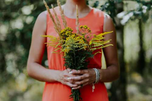 Woman in a red dress with flowers outdoors