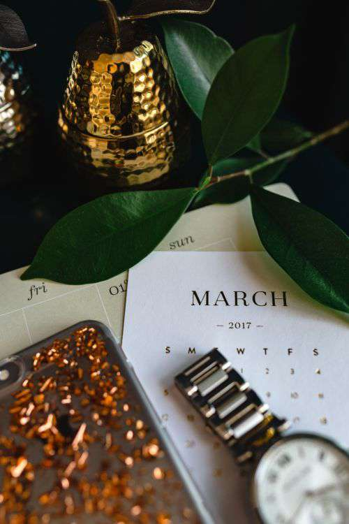 Home office desk with Macbook, iPhone, calendar, watch & organizer
