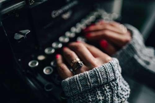 Woman typing on an old typewriter