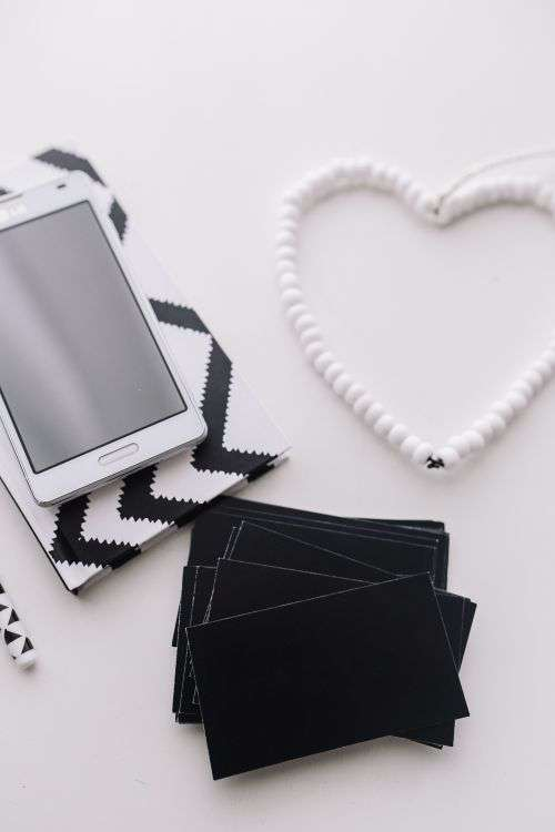 Black-and-white notebook and a white smartphone with various items