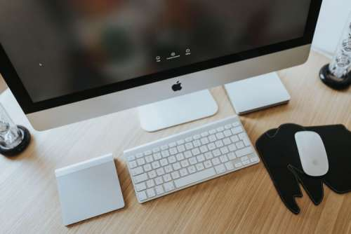 White Apple iMac computer with elephant mousepad